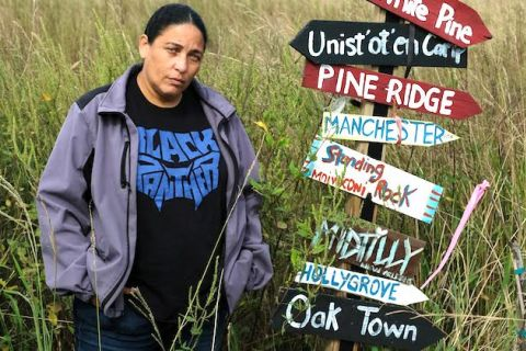 A Native woman wearing a blue hoodie stands next to a pole with signs symbolizing historic fights