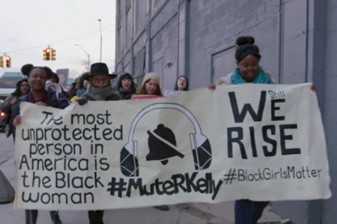 "Black women march in multicolored coats and clothes while holding tan banner with black text reading ""WE RISE"" and ""The most unprotected person in America is the Black woman"" and ""#MuteRKelly"" in front of grey building and sky."