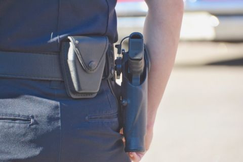 Close-up of white police officer's arm and waistline, with gun in holster showing.