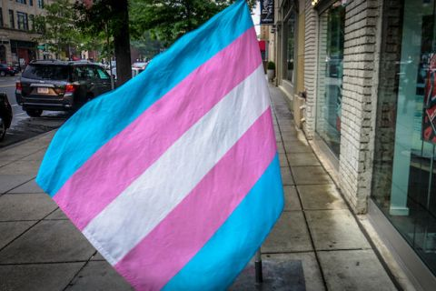 Trans flag hanging above a city street. Flag has blue, pink and white stripes.