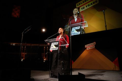 "Ava DuVernay. Black woman with black locs in red blouse and black skirt speaks behind glass podium with black sign with red and yellow panels and black text that spells ""COLOR OF CHANGE"" and video screen."