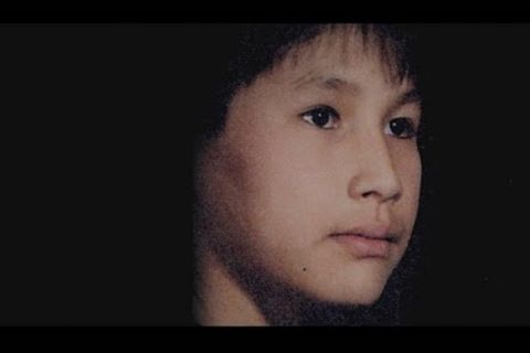 Joe Four Horns. Indigenous boy with black hair poses in front of black background.