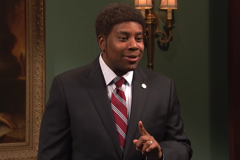 Kenan Thompson. Black man in navy suit with red and gray striped tie and white shirt holds finger in front of green wall and brown painting frame.