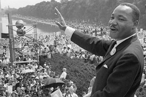 The Reverend Dr. Martin Luther King Jr. Black-and-white photograph of Black man waving to spectators surrounding reflecting pool and green shrubs.