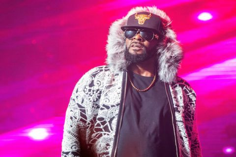 R. Kelly. Black man pauses onstage wearing black sunglasses, a black, white and black hoodie with gray fur trim, and a gold and black Chicago Bulls Hat. There is a hot pink background.