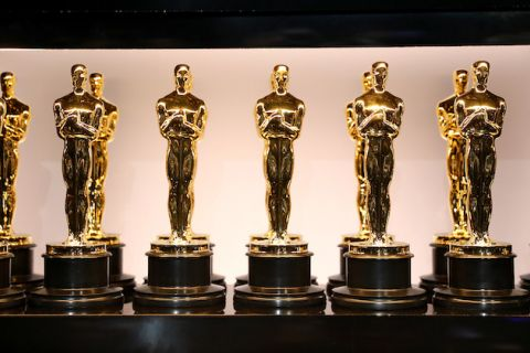 Gold Oscar statues in multiple rows on brown pedestals in front of beige and black background