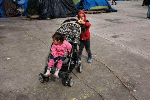 A small boy wearing a red hooded sweatshirt pushes a small girl wearing pink as she sits in her stroller. Both are playing in the El Barretal migrant shelter in Tijuana, Mexico on January 15, 2019.