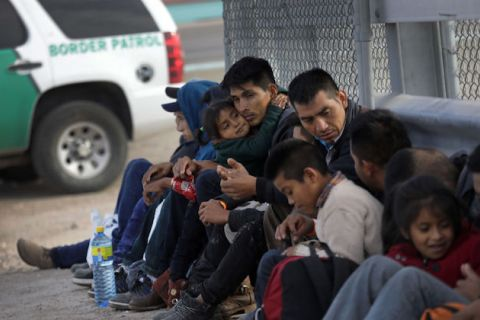 Central American fathers and their children cuddle and lean against a fence as they wait to be taken into custody after crossing into El Paso, Texas from Mexico on February 01, 2019.