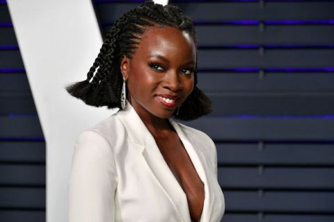 Black woman in white suit jacket and long dangling earrings with head turned to the side smiling in front of a black slatted window,