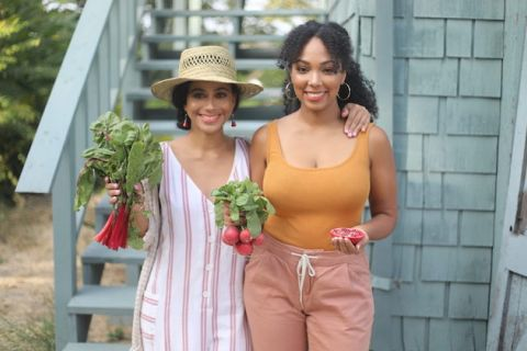 Two women of color stand next to each other in front of a staircase in the country, each holding vegetables and fruit that appear to be plucked fresh from a garden.