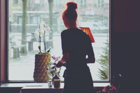 Woman with red hair in silohuette puts silverware on table while standing in front of a window in daylight, there is a white orchid in a yellow pot and a lamp with a red shade, trees and benches outside