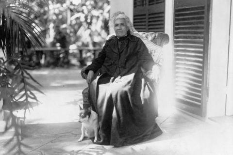 Black and white photo of woman of color seated outdoors on a porch. facing slightly left with a small dog at her feet and palm trees behind them.