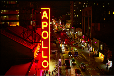 The sign for Harlem's Apollo theater lit up in red against a cityscape at night.