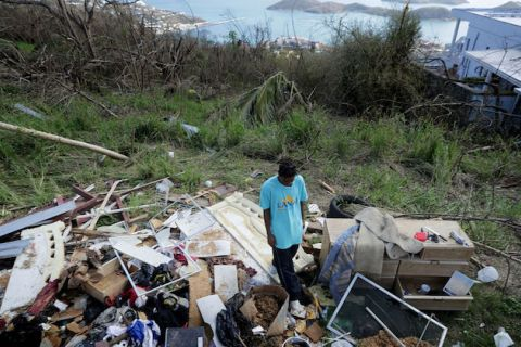 Black man stands among his family's ruined possessions