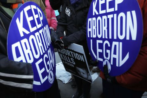"Protesters hold signs. Two blue and white signs say, ""Keep abortion legal."" One black and white sign says, ""Abortion kills a person."""