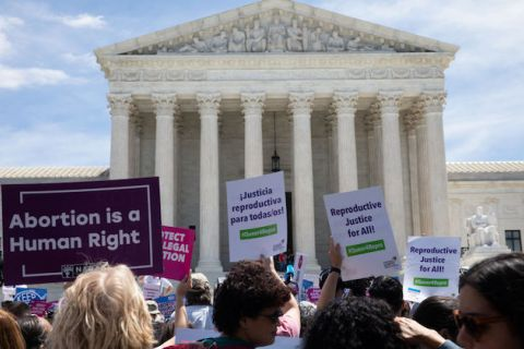 women hold signs in support of abortion rights outside Supreme Court