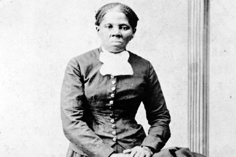 Harriet Tubman. Black and white photo of a Black woman in a dark-colored dress with a white bow at the next and metal buttons down the center.