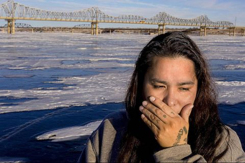 Native woman with hand to her mouth standing in front of water and bridge