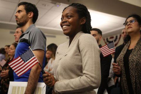 Smiling black woman wearing grey sweater holding a small american flag at a naturalization ceremony with two other people standing on both sides of her also holding flags