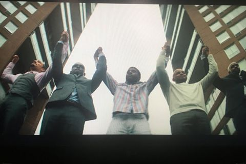 When They See Us: Four Black and one Latinx Man on a stage with hands linked in the air.