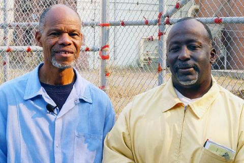 Lonnie Morris and Richard Lathan. Two middle-aged Black men in prison uniforms, blue and yellow, in front of a gate.