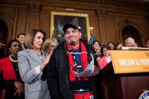 Man wearing purple baseball cap, black jacket and red and blue shirt stands behind a podium and is surrounded by House democrats.