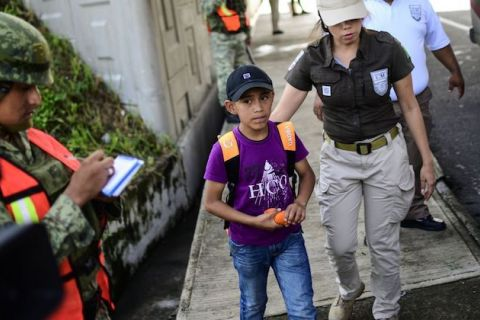 A young boy wearing a school backpack and purple t-shirt walks with a Mexican immigration agent.