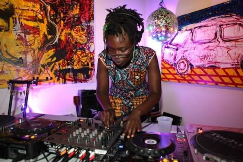 A Black woman with locs stands over two turntables at a party