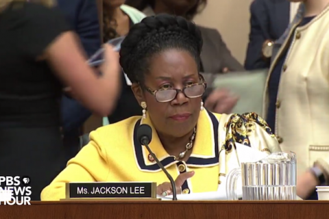 Sheila Jackson Lee. Black woman with goddess braid crown in yelow jacket with black and white details sits behind a microphone.