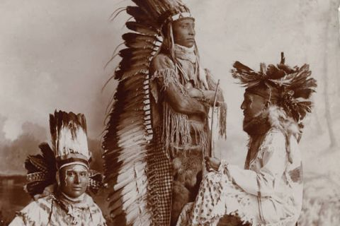Three Native American men from the Sioux Tribe wearing Ghost Dance costumes.