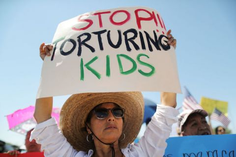 "woman wearing white shirt and straw hat holds a white sign with red, black and green lettering that reads, ""Stop Torturing Kids"""