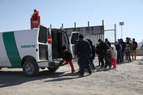 group of people stand in single-file line as they board a green and white border patrol van.