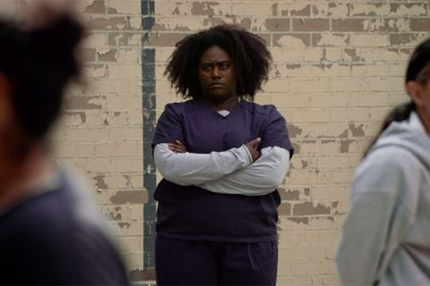 Danielle Brooks. In character. Black woman with Afro wearing blue prison uniform and white long sleeve t-shirt as she stands in front of brick wall.