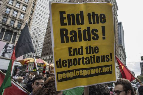 "A protestor holds up a yellow sign captioned ""End the Raids! End the deportations."""