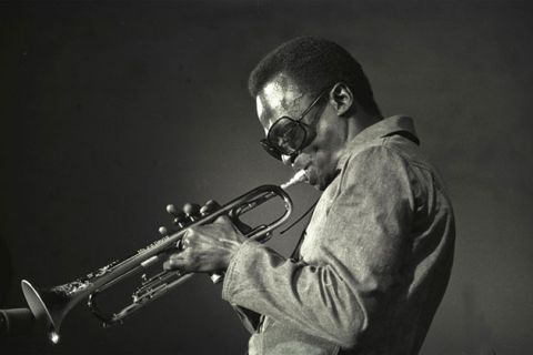 Miles Davis. Profile of middle-aged Black man wearing dark glasses, dark suit and blowing a trumpet.