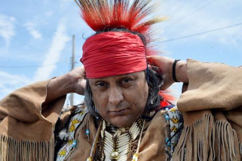 An Apache man puts on a red headress