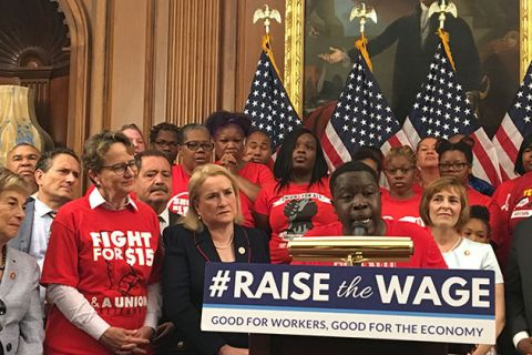 "Raise the Wage Vote. Sea of Black women wearing red T-shirts reading ""Fight for 15,"" with one woman standing behind a podium."