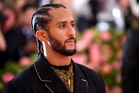 Colin Kaepernick. Black man with cornrows going back and facial hair, wearing a black suit jacket with gold details.
