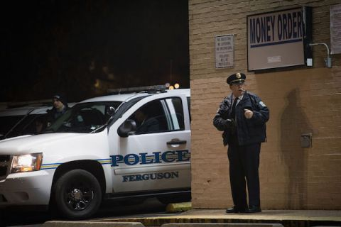 White police officer stands in front of a store at night with police car visible in the background.