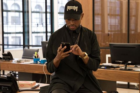 Twitter Bias. Black man wearing all black with black baseball cap looking down at his phone and typing.