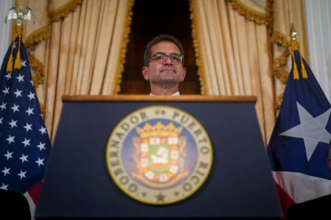 Pedro Pierluisi stands behind a podium
