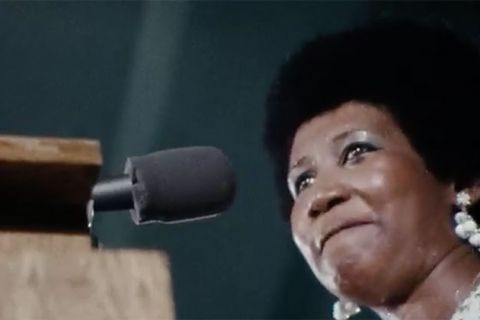 Amazing Grace. Black woman with Afro standing in front of microphone on a podium.