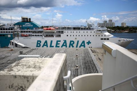 "Balearia ferry docked in Florida. White ferry with blue writing that reads ""Balearia"" on it against a blue sky with white clouds"