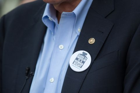a button about insulin availability pinned to a blue suit jacket