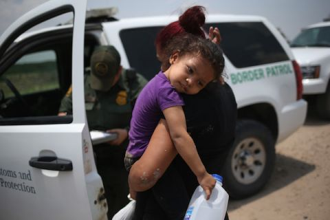 A little girl wearing a purple shirt is held in her mother's arms as the woman speaks to a Border Patrol agent.
