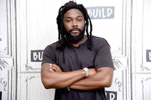 Jason Reynolds. Black man with locs wearing dark gray t-shirt in front of white step and repeat.