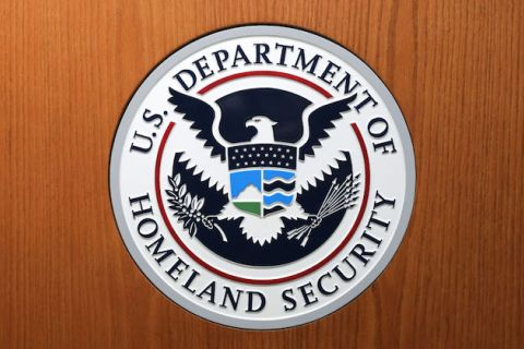 Department of Homeland Security's white, navy, red and green seal on a woodgrain background
