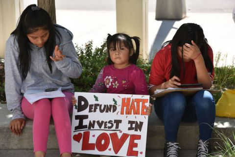 "Three young girls with dark hair sit on a curb holding a sign that reads, ""Defund hate, invest in love."""