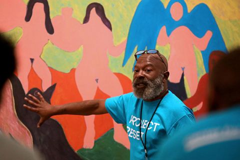 Project Reset. Older Black man with bald hand standing in front of colorful artwork.