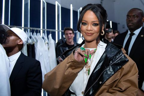 Rihanna. Black woman with hair pulled back and long bangs wearing a tan colored jacket and white shirt with long green nails.